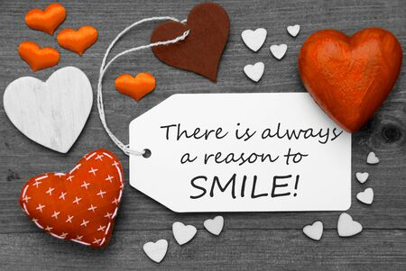 hot spot: Label With Orange Textile Hearts On Wooden Gray Background. English Quote There Is Always A Reason To Smile. Retro Or Vintage Style. Black And White Image With Colored Hot Spot.