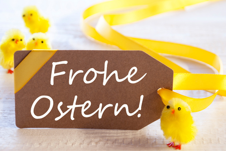 Ostern: One Brown Label With Yellow Ribbon. German Text Frohe Ostern Means Happy Easter. Card For Easter Greetings On Wooden Background Stock Photo