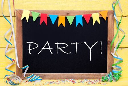 like english: Chalkboard With English Text Party. Party Decoration Like Streamer, Confetti And Bunting Flags. Yellow Wooden Background With Vintage, Retro Or Rustic Syle