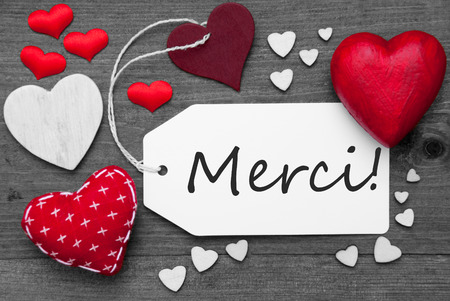 hot spot: Label With Red Textile Hearts On Wooden Gray Background. French Text Merci Means Thank You. Retro Or Vintage Style. Black And White Image With Colored Hot Spot.