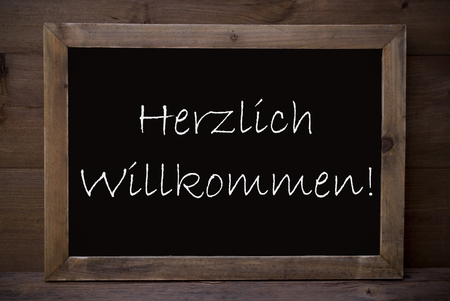 willkommen: Brown Blackboard With German Text Herzlich Willkommen Means Welcome As Greeting Card. Wooden Background. Vintage Rustic Style.