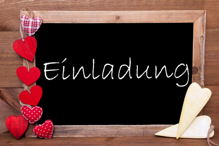 welcom: Chalkboard With German Text Einladung Means Invitation. Many Red Textile And Wooden Yellow Hearts. Wooden Background With Vintage, Rustic Or Retro Style. Stock Photo