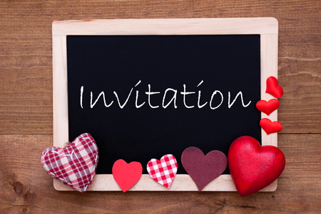 english text: Blackboard With English Text Invitation. Red Textile Hearts. Wooden Background With Vintage, Rustic Or Retro Style.