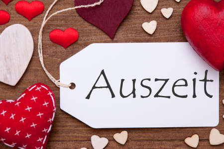 auszeit: Label With Red Textile Hearts On Wooden Gray Background. German  Auszeit Means Downtime. Retro Or Vintage Style. Macro Or Close Up Of One Label