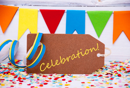 like english: Label With English Text Celebration. Party Decoration Like Streamer, Confetti And Bunting Flags. White Wooden Background With Vintage, Retro Or Rustic Syle Stock Photo