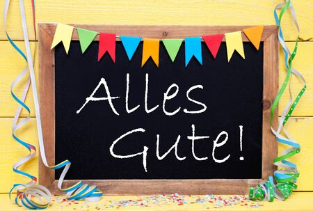 best wishes: Chalkboard With German Text Alles Gute Means Best Wishes. Party Decoration Like Streamer, Confetti And Bunting Flags. Yellow Wooden Background With Vintage, Retro Or Rustic Syle