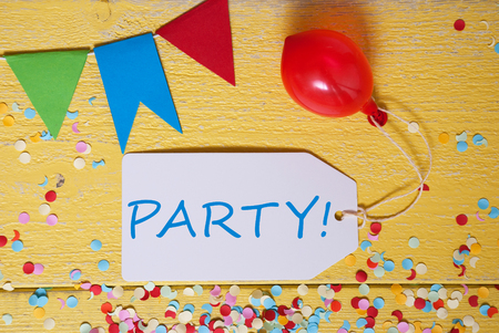 like english: One Label With English Text Party. Decoration Like Balloon, Confetti And Bunting Flags. Yellow Wooden Background With Vintage, Retro Or Rustic Syle