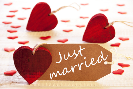 english text: Romantic Label With Many Hearts. English Text Just Married on Wooden Background
