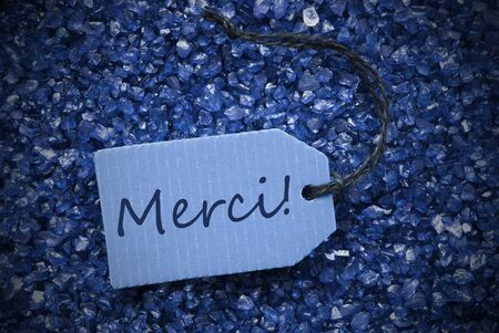 thankfulness: One Blue Label Or Tag With Black Ribbon On Blue And Purple Small Stones As Background With French Text Merci Means Thank You With Frame Stock Photo