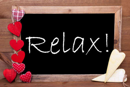 downtime: Chalkboard With English Text Relax. Many Red Textile And Wooden Yellow Hearts. Wooden Background With Vintage, Rustic Or Retro Style.