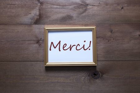 french text: One Golden Picture Frame On Wooden Background. French Text Merci Means Thank You. Rutic Vintage Or Retro Style. Background With Copy Space As Greeting Card Stock Photo
