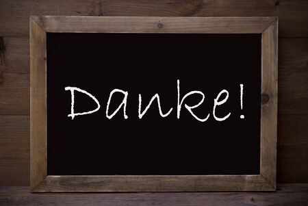 thankfulness: Brown Blackboard With German Text Danke Means Thank You As Greeting Card. Wooden Background. Vintage Rustic Style.