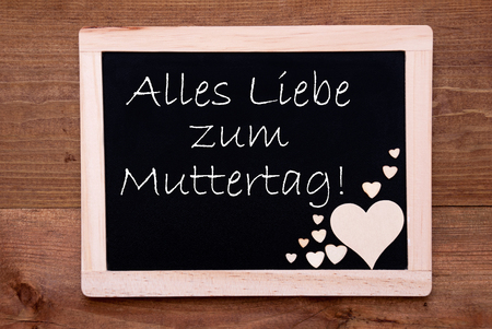 Liebe: Blackboard With German Text Alles Liebe Zum Muttertag Means Happy Mothers Day. Brown Wooden Hearts. Wooden Background With Vintage, Rustic Or Retro Style. Stock Photo