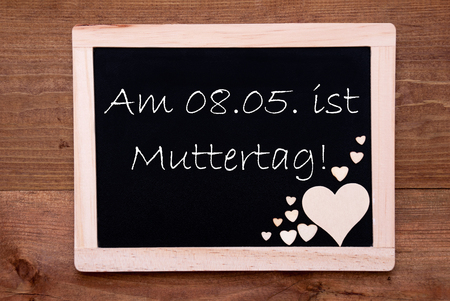 ist: Blackboard With German Text Am 8. Mai Ist Muttertag Means Happy Mothers Day. Brown Wooden Hearts. Wooden Background With Vintage, Rustic Or Retro Style.