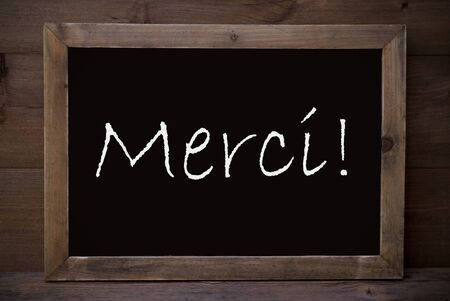 french text: Brown Blackboard With French Text Merci Means Thank You As Greeting Card. Wooden Background. Vintage Rustic Style.
