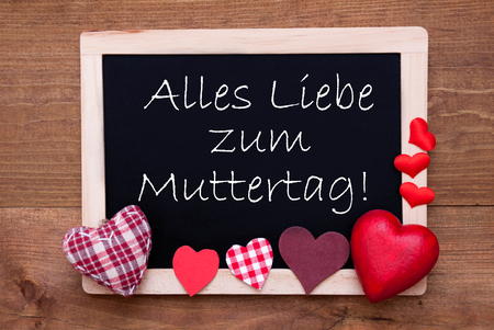 Liebe: Blackboard With German Text Alles Liebe Zum Muttertag Means Happy Mothers Day. Red Textile Hearts. Wooden Background With Vintage, Rustic Or Retro Style.