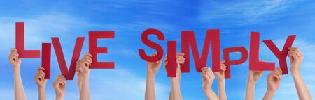 simply: Many Caucasian People And Hands Holding Red Letters Or Characters Building The English Word Live Simply On Blue Sky