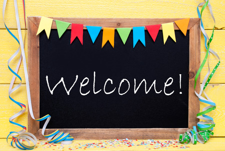 like english: Chalkboard With English Text Welcome. Party Decoration Like Streamer, Confetti And Bunting Flags. Yellow Wooden Background With Vintage, Retro Or Rustic Syle