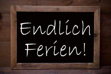 ferien: Brown Blackboard Or Chalkboard With German Text Endlich Ferien Means Happy School Vacation As Greeting Card. Wooden Background. Vintage Rustic Style.