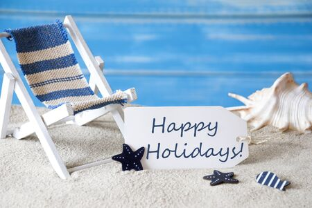 symbolized: Summer Label With English Text Happy Holidays. Blue Wooden Background. Card With Holiday Greetings. Beach Vacation Symbolized By Sand, Deck Chair And Shell. Stock Photo