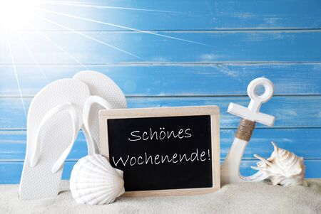 symbolized: Chalkboard With German Text Schoenes Wochenende Means Happy Weekend. Blue Wooden Background. Sunny Summer Card With Holiday Greetings. Beach Vacation Symbolized By Sand, Flip Flops, Anchor And Shell. Stock Photo