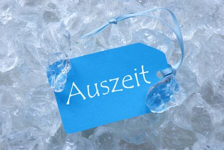 auszeit: Light Blue Label With Blue Ribbon On White Transparent Curshed Ice Cubes As Background. German Text Auszeit Means Downtime For Cool Greetings.Close Up Or Macro View.