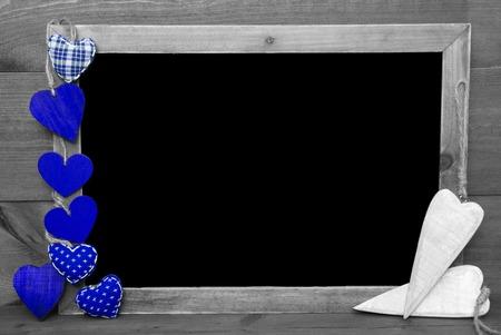 corazones azules: Pizarra con copia espacio para el anuncio. Muchos corazones azules. Fondo de madera con la vendimia, rústica o estilo retro. Imagen blanco y negro con manchas de color calientes. Foto de archivo