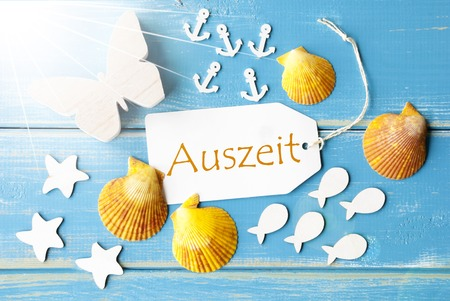 auszeit: Flat Lay View Of Label With German Text Auszeit Means Downtime. Sunny Summer Greeting Card. Butterfly, Shells And Fishes On Blue Wooden Background