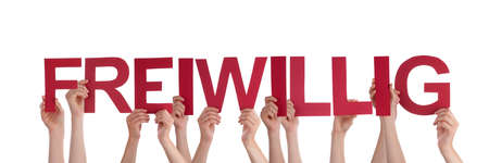 voluntary: Many Caucasian People And Hands Holding Red Straight Letters Or Characters Building The Isolated German Word Freiwillig Which Means Voluntary On White Background Stock Photo