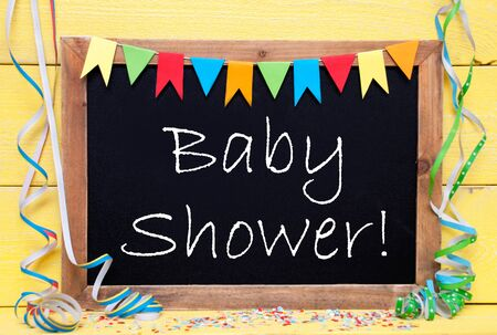 like english: Chalkboard With English Text Baby Shower. Party Decoration Like Streamer, Confetti And Bunting Flags. Yellow Wooden Background With Vintage, Retro Or Rustic Syle