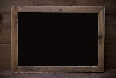 your text: Brown Blackboard With Copy Space, Free Text Or Your Text Here As Greeting Card Or Advertisement. Wooden Background. Vintage Rustic Style. Stock Photo