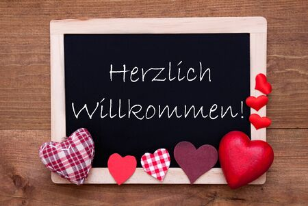 willkommen: Blackboard With German Text Herzlich Willkommen Means Welcome. Red Textile Hearts. Wooden Background With Vintage, Rustic Or Retro Style. Stock Photo