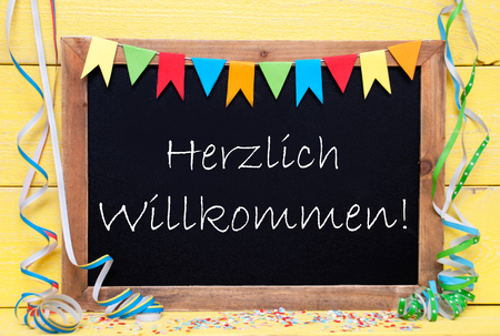 willkommen: Chalkboard With German Text Herzlich Willkommen Means Welcome. Party Decoration Like Streamer, Confetti And Bunting Flags. Yellow Wooden Background With Vintage, Retro Or Rustic Syle