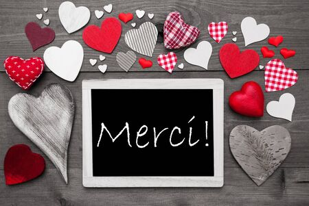 french text: Chalkboard With French Text Merci Means Thank You. Many Red Textile Hearts. Grey Wooden Background With Vintage, Rustic Or Retro Style. Black And White Style With Colored Hot Spots