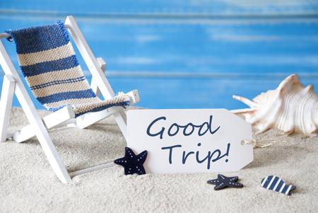bonne aventure: Étiquette d'été avec l'anglais texte Good Trip. Arrière-plan en bois bleu. Carte Avec salutations de vacances. Beach Vacation symbolisés par sable, chaise longue et Shell.