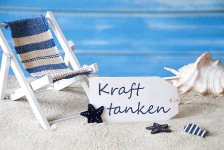symbolized: Summer Label With German Text Kraft Tanken Means Relaxation. Blue Wooden Background. Card With Holiday Greetings. Beach Vacation Symbolized By Sand, Deck Chair And Shell.