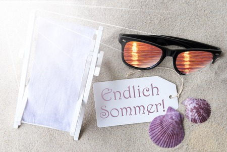 sommer: Sunny Summer Label With German Text Endlich Sommer Means Hello Summer. Flat Lay View. Summer Decoration With Deck Chair, Seashells And Sunglasses. Greeting Crad With Sand Background