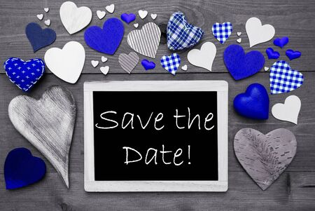 hot date: Chalkboard With English Text Save The Date. Many Blue Textile Hearts. Grey Wooden Background With Vintage, Rustic Or Retro Style. Black And White Style With Colored Hot Spots Stock Photo