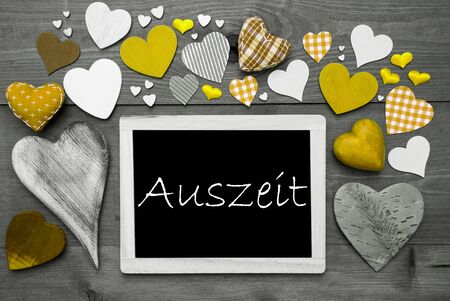auszeit: Chalkboard With German Text Auszeit Means Relax. Many Yellow Textile Hearts. Grey Wooden Background With Vintage, Rustic Or Retro Style. Black And White Style With Colored Hot Spots Stock Photo
