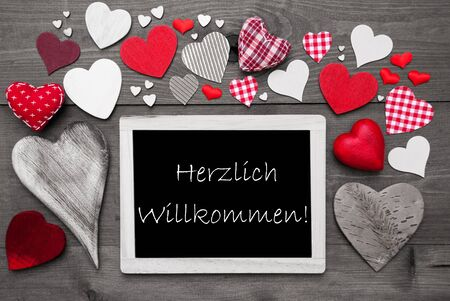 willkommen: Chalkboard With German Text Herzlich Willkommen Means Welcome. Red Textile Hearts. Grey Wooden Background With Vintage, Or Retro Style. Black And White Style With Colored Hot Spots