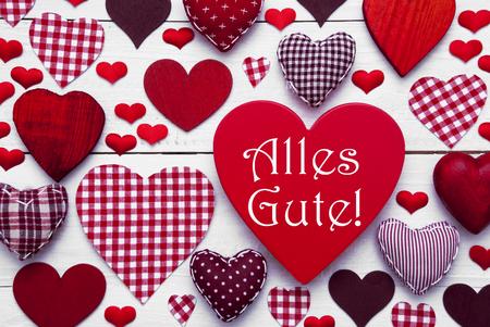 Cuore Rosso Texture con testo tedesco Alles Gute Significa Auguri. Sfondo bianco in legno. Tessili Cuori che sono punteggiate e strisce. Biglietto di auguri per auguri di compleanno