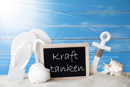symbolized: Chalkboard With German Text Kraft Tanken Means Relaxation. Blue Wooden Background. Sunny Summer Card With Holiday Greetings. Beach Vacation Symbolized By Sand, Flip Flops, Anchor And Shell.