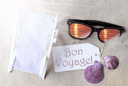 french text: Sunny Summer Label With French Text Bon Voyage Means Good Trip. Flat Lay View. Summer Decoration With Deck Chair, Seashells And Sunglasses. Greeting Crad With Sand Background Stock Photo