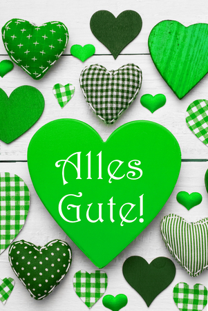 best wishes: Green Vertical Heart Texture With German Text Alles Gute Means Best Wishes. White Wooden Background. Textile Hearts Which Are Dotted and Striped. Greeting Card For Birthday Wishes