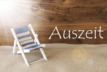 auszeit: Sunny Summer Greeting Card With Sand And Aged Wooden Background. German Text Auszeit Means Relax. Deck Chair For Holiday Or Vacation Feeling.