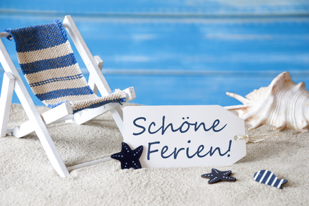symbolized: Summer Label With German Text Schoene Ferien Means Happy Holidays. Blue Wooden Background. Card With Holiday Greetings. Beach Vacation Symbolized By Sand, Deck Chair And Shell.
