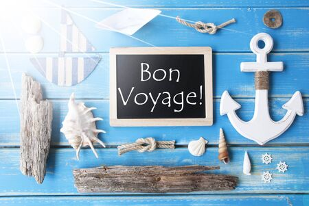 nautic: Flat Lay Of Chalkboard On Blue Wooden Background. Sunny Nautic Or Maritime Summer Decoration As Holiday Greeting Card. French Text Bon Voyage Means Good Trip
