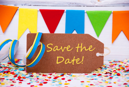 like english: Label With English Text Save The Date. Party Decoration Like Streamer, Confetti And Bunting Flags. White Wooden Background With Vintage, Retro Or Rustic Syle Stock Photo