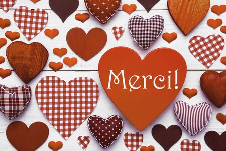 french text: Brown Heart Texture With French Text Merci Means Thank You. White Wooden Background. Textile Hearts Which Are Dotted and Striped. Greeting Card For Valentines Day Or Thanksgiving Stock Photo