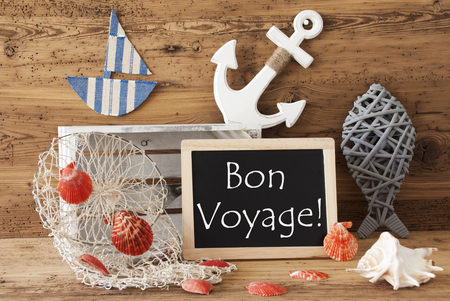 french text: Blackboard With Nautical Summer Decoration And Wooden Background. French Text Bon Voyage Means Good Trip. Fish, Anchor, Shells And Fishnet For Maritime Contex.